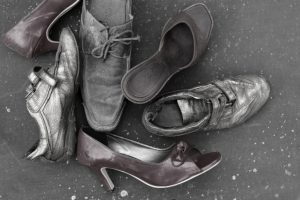 Various abandoned shoes laid on the ground, overhead shot in black and white